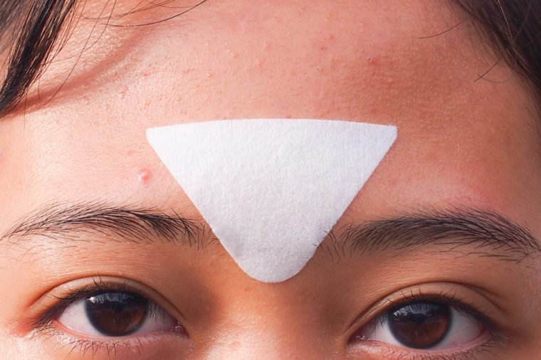Closeup young woman with a pore strip on her T-zone to remove blackheads