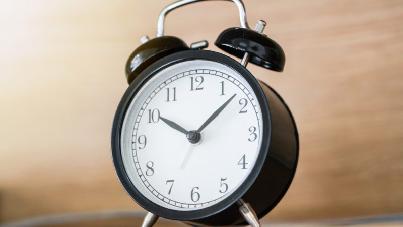 Black alarm clock on the headboard bed shelf with sunlight from the window in the morning, time deadline concept