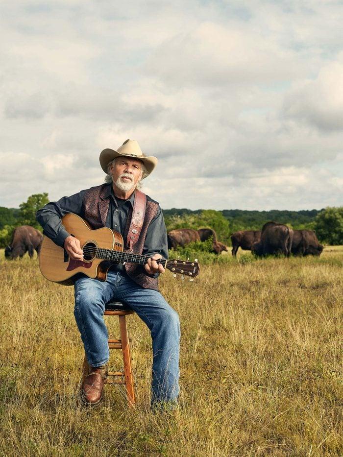 Freddie Fuller playing guitar in field