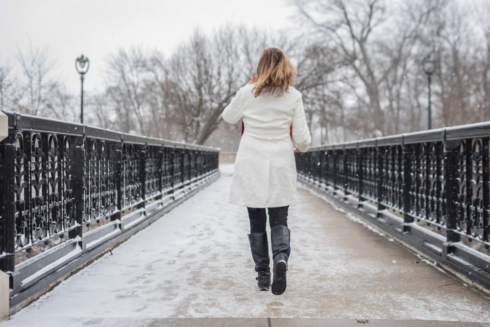 one woman walking on bridge in city park with snow falling and back to camera
