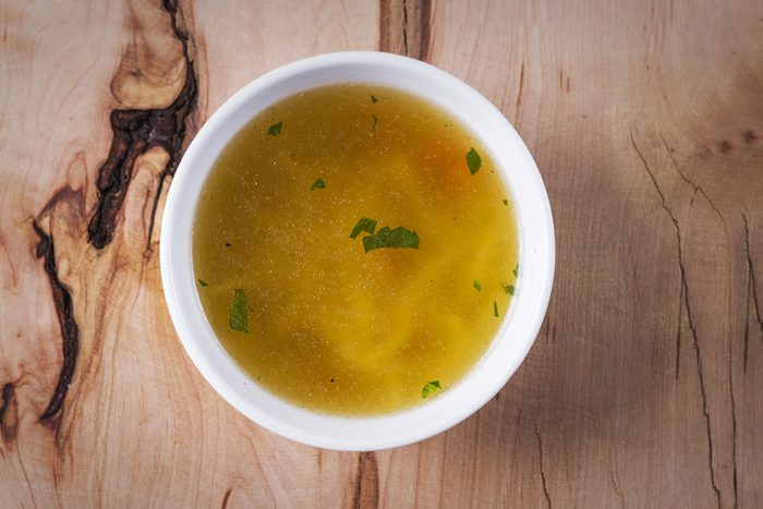 Chicken soup on a rustic wooden table, top view