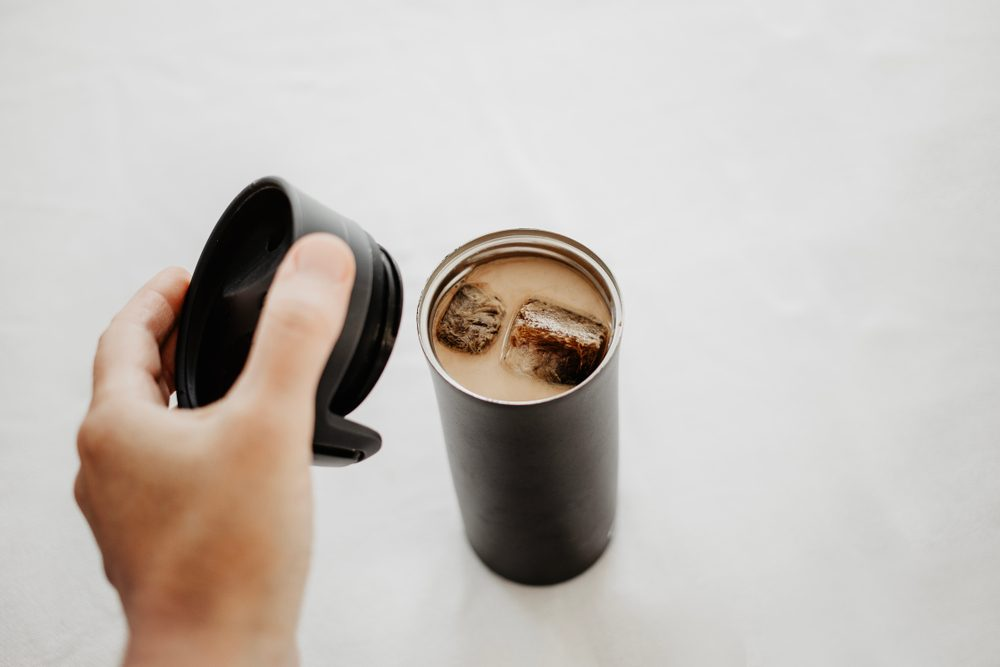 Iced coffee to go. Frozen coffee ice cubes in vacuum flask poured with milk. Hand putting a thermos lid over the bottle. White background, body parts, personal point of view shot. Isolated, copy space