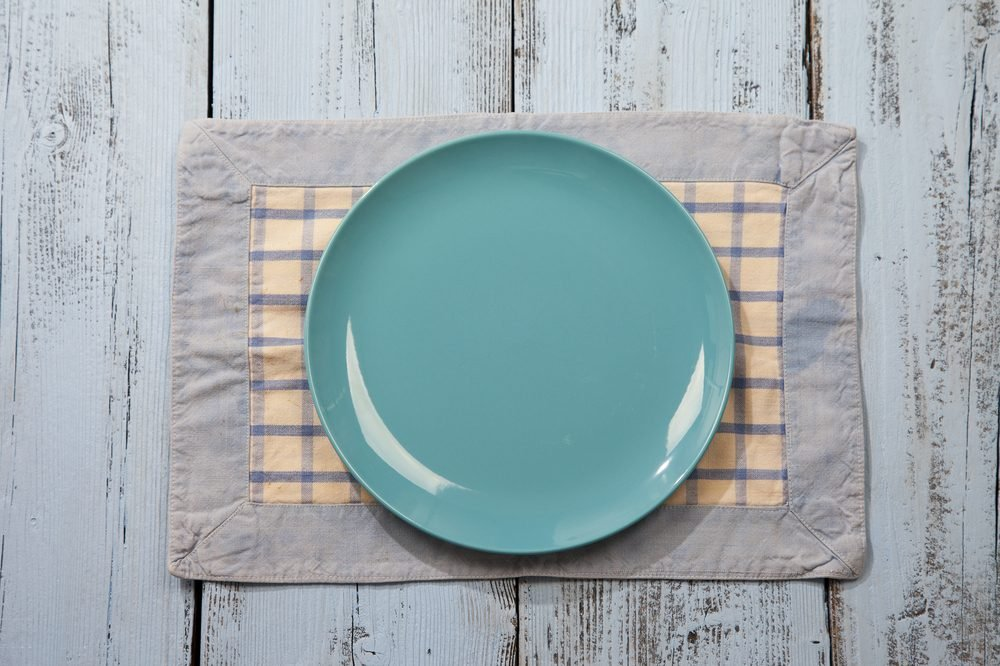 Empty plate on light blue wooden background