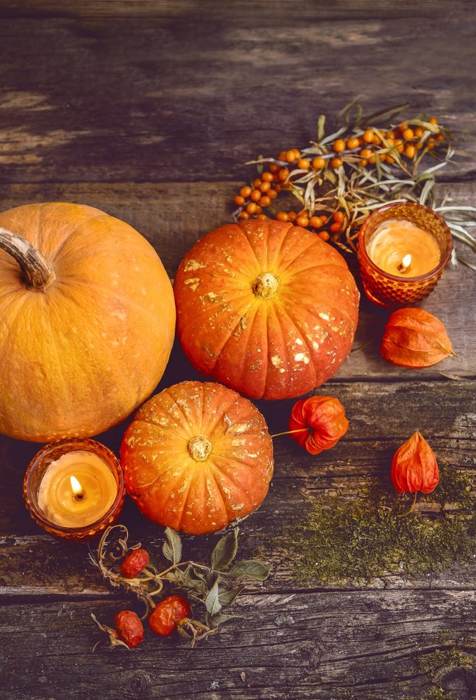 beautiful autumn composition with pumpkins. autumn cozy still life. pumpkins, autumn leaves and candles on wooden background. soft focus, top view