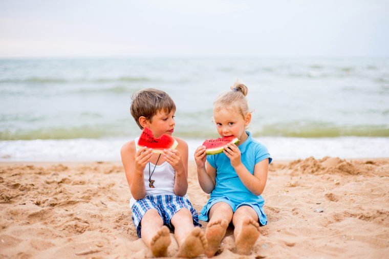 two children eating watermelon on the beach