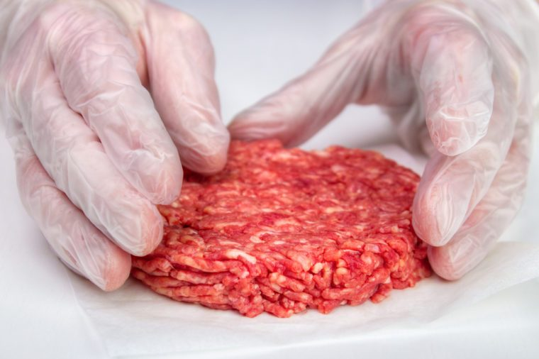 Hand shaping burger patty with vinyl gloves for hygiene