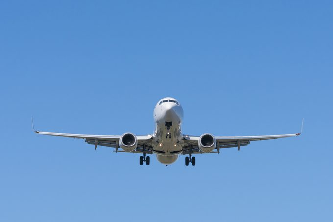 Front view of a jet passenger airplane approaching an airport for landing