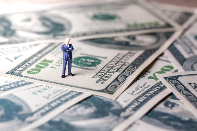 Miniature figurine toys standing on dollar with money and work concept. Focus on the businessman.