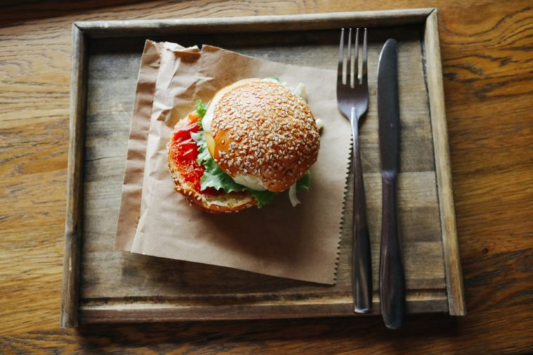 Burger with meat. Homemade cheese burger or hamburger on a wood plate served to put on wood table with copy space. Fast food for breakfast or lunch.