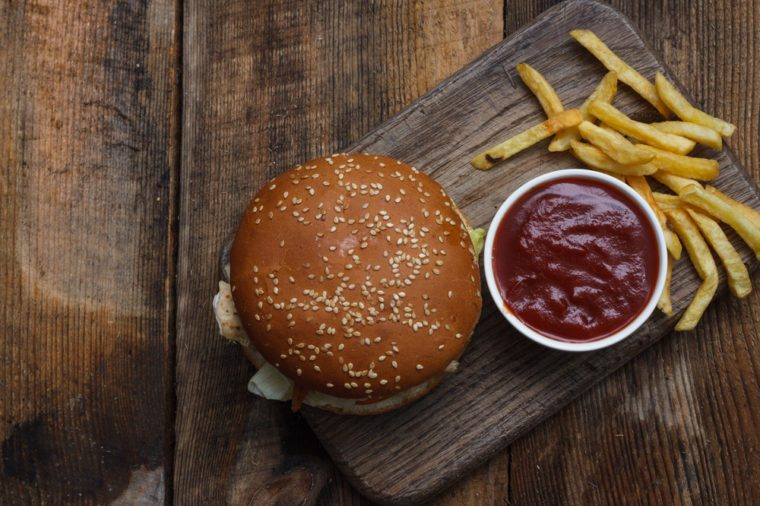 Fresh home-made hamburger served on wood. Wooden background. Tasty hamburger with chicken. View from above.