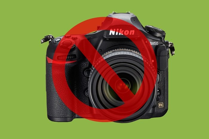 Camera on green background with cancel sign over it