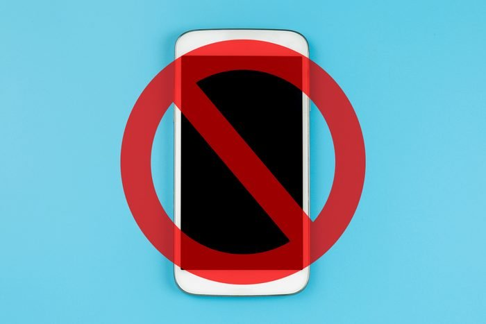 personal cell phone on blue background with a cancel sign over it