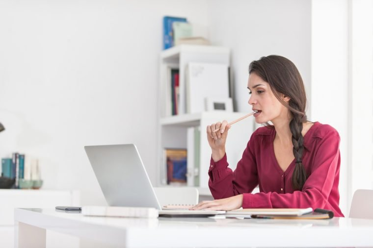 Portrait of a dark braided hair woman chewing her pencil while working home on her laptop. She is sitting at a big white table in a luminous place, wearing casual clothes. Focus on the woman