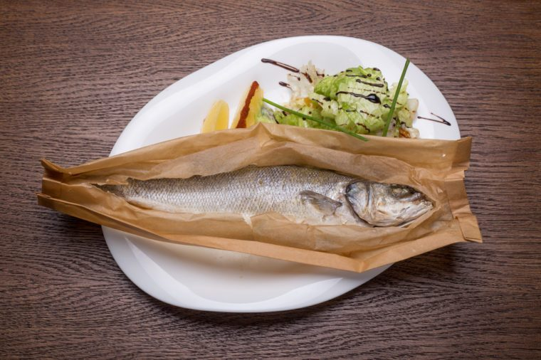 Grilled sea bass fish in paper with vegetables on wooden table