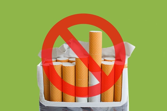 Cigarettes on green background with cancel sign over it