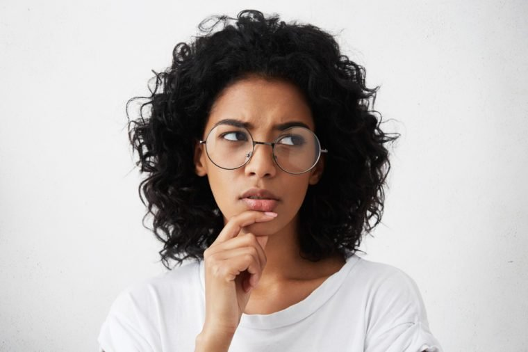 Doubtful young woman wearing trendy round eyeglasses frowning and looking sideways with indecisive and perplexed facial expression, touching her chin while can't decide what to wear on party