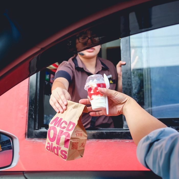 Unidentified customer receiving hamburger and ice cream after order and buy it from McDonald's drive thru service
