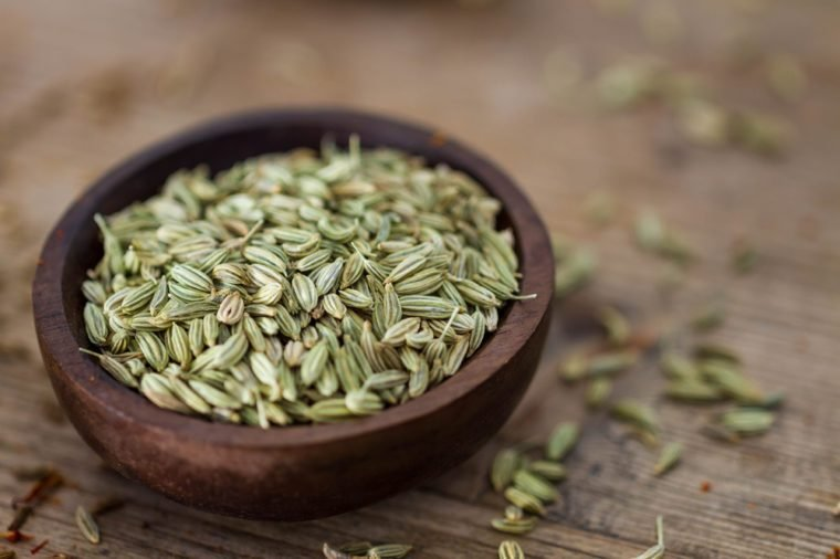 Fennel seeds in a small wooden bowl on an old wooden table.