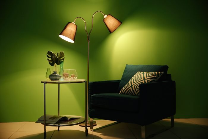 Armchair, lamp and table with home decor on green wall background