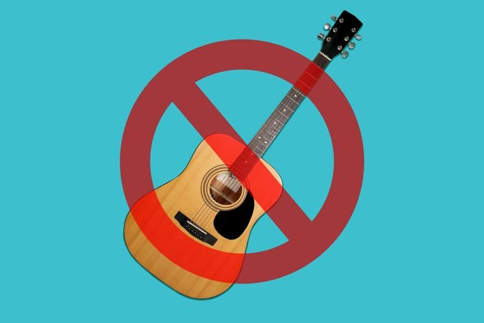 Guitar on blue background with cancel sign over it