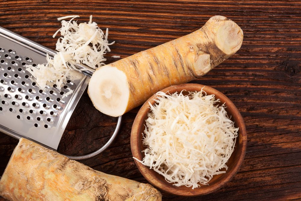 Fresh grated Horseradish roots on wooden table. Rustic style from above.