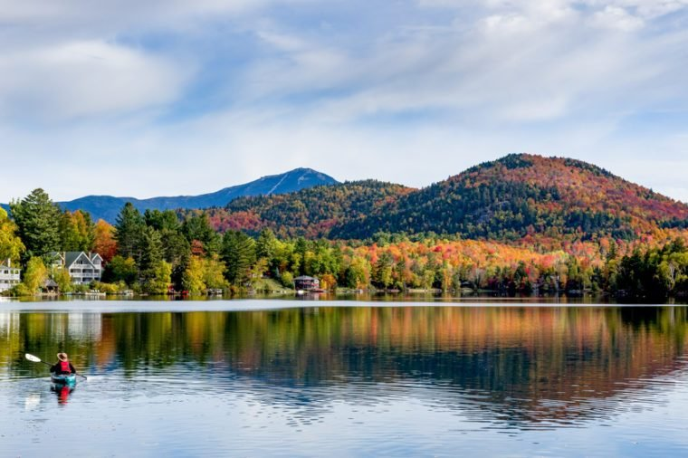 A panoramic view of Mirror Lake in Lake Placid, New York, on a sunny autumn day with colorful fall foliage on the mountains in the background