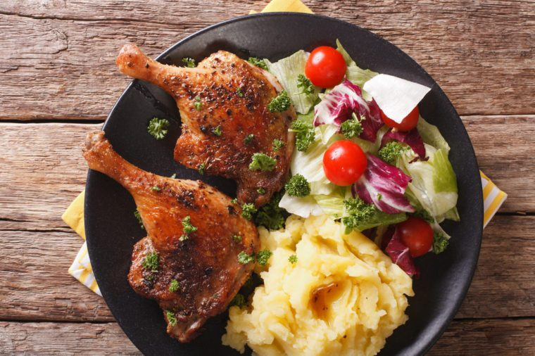 roasted duck leg with mashed potatoes side dishes and fresh salad on the plate closeup. horizontal view from above