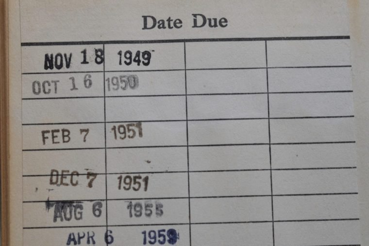 Closeup of a vintage library book with date due stamps from November 1949 through April 1959.