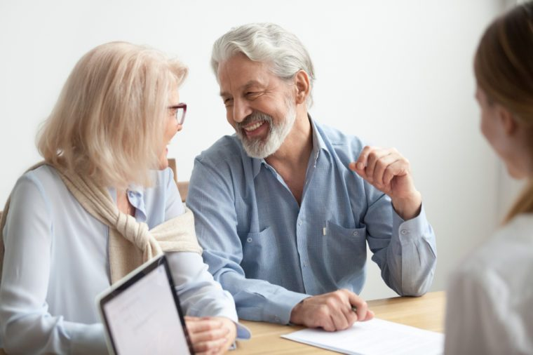 Happy senior family talking smiling at meeting with financial advisor, older clients ready to buy medical health life insurance consulting broker, aged retired couple real estate deal about to sign