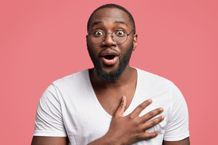 Studio shot of excited glad African American male model keeps hand on chest, looks with surprise and amazement, doesn`t expect to recieve congratulation from colleagues. Pleased dark skinned guy
