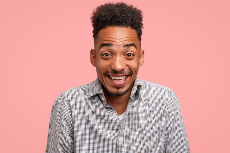 Cheerful dark skinned guy has trendy haircut, giggles happily, dressed in checkered shirt, stands against pink background, models in studio. Smiling African American man expresses positive emotions