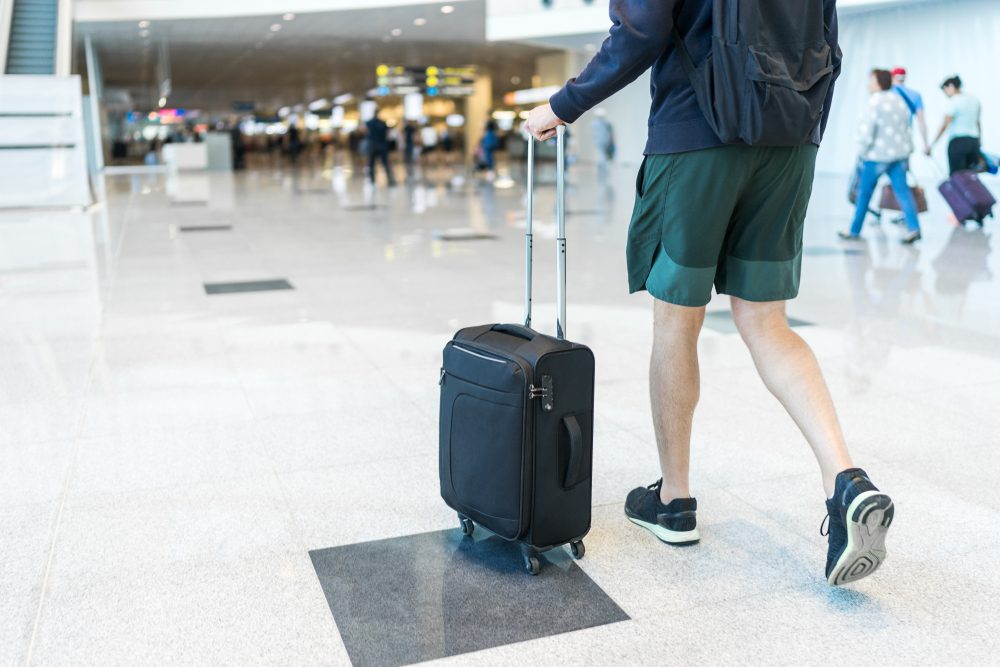 Young man wearing shorts and sneakers is walking through the airport holding a small-sized black suitcase with 4 wheels