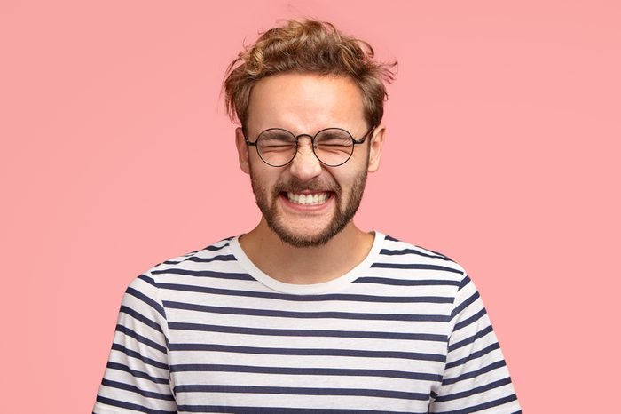 Photo of attractive cheerful man laughs positively at camera, keeps eyes closed, dressed in casual striped t shirt, round spectacles, models in studio against pink background. Happy hipster indoor