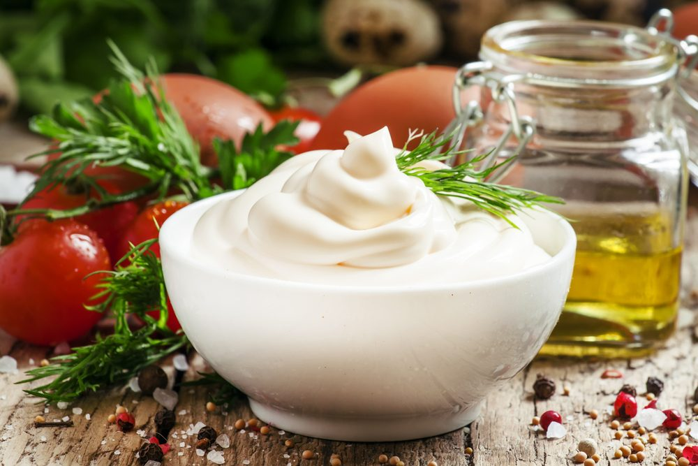 Homemade mayonnaise sauce in a white bowl, jar with olive oil, eggs, salt, spices, mustard, herbs, cherry tomatoes on old wooden background, selective focus