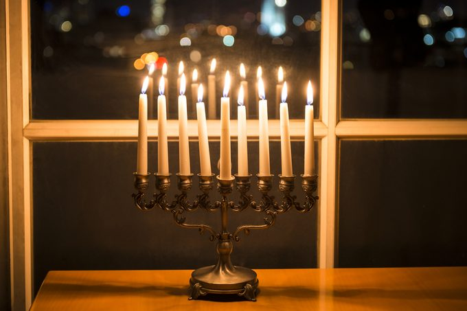 Low key image of with menorah (candlestick with 8 candles) by the window with the night view on Tel Aviv, Israel. Candles burning on the Jewish holiday Hanukkah menorah stock image.
