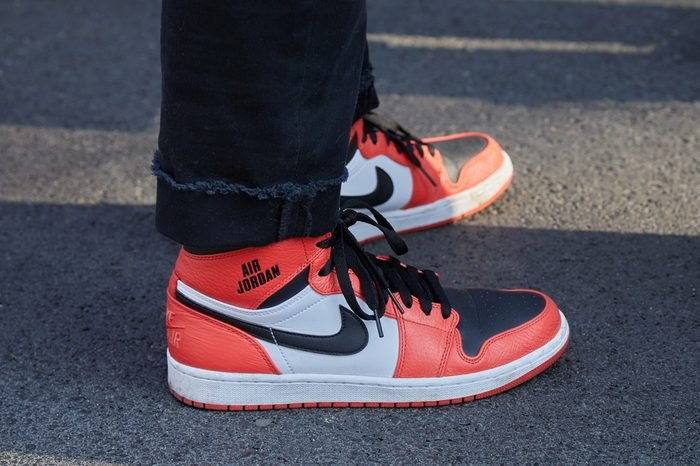 MILAN - FEBRUARY 27: Man with orange Nike Air Jordan shoes before Giorgio Armani fashion show, Milan Fashion Week street style on February 27, 2017 in Milan.