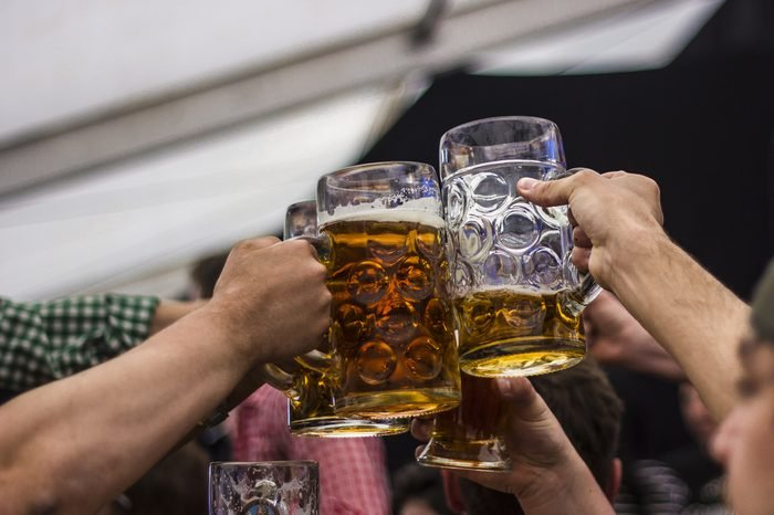 German beer stein glasses cheers in Oktoberfest. Concept: Beer drinking festival, German culture, Lifestyle, Party, Celebration