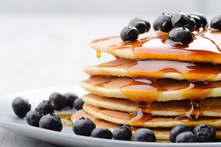 Delicious pancakes close up, with fresh blueberries and maple syrup