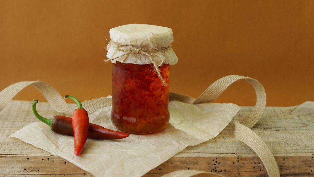 Pepper chili jam in jar on paper and wooden background