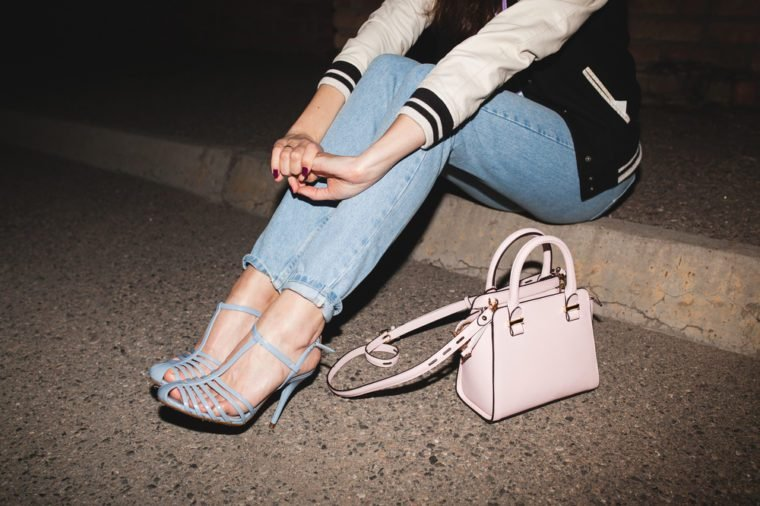 young stylish hipster woman, swag outfit, jeans, cool accessories, sitting on ground, pink purse, legs close up, details, shoes