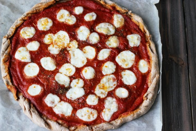 Wholegrain pizza Margherita with mozzarella on a brown wooden background