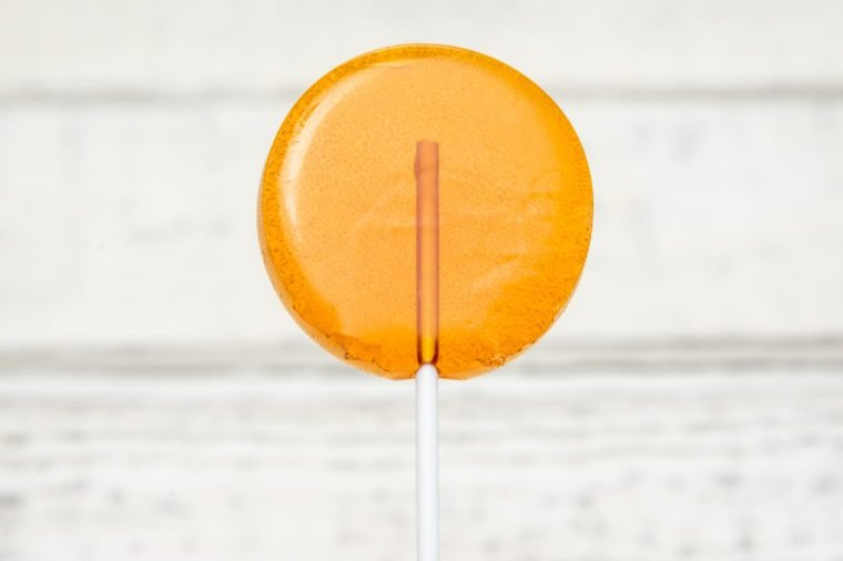Orange candy, sweet candy on a stick, caramel