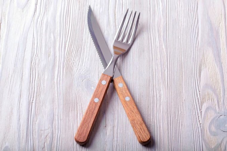 Knife and fork crossed. Knife and fork with wood handle