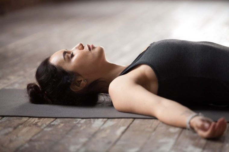 Young sporty woman practicing yoga, lying with eyes closed in Dead Body or Corpse pose, Savasana exercise, working out wearing sportswear top, resting after yoga, indoor close up photo, studio