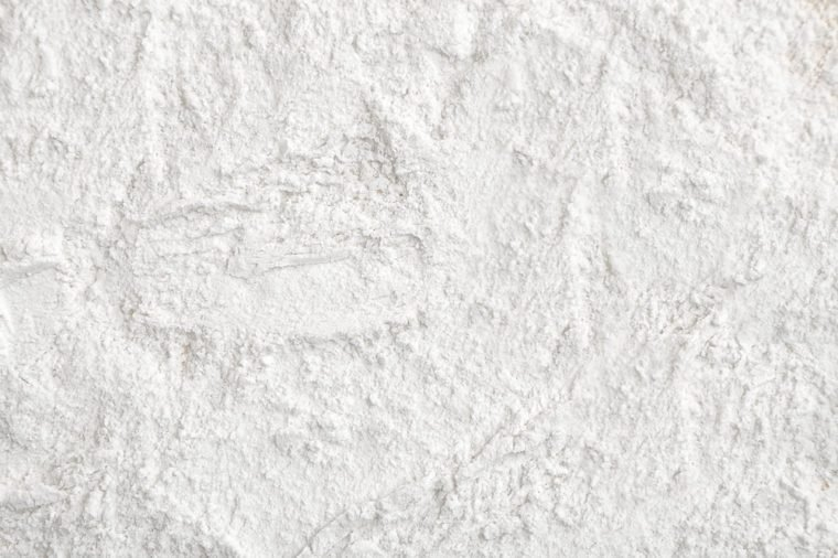 Flour close up background. A pile of flour on a white background. Spilled flour. Flour texture