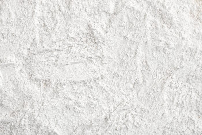 Flour close up background. A pile of flour on a white background. Spilled flour. Flour texture