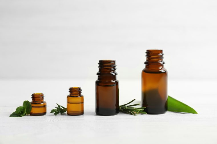 Bottles with essential oils and fresh herbs on light background