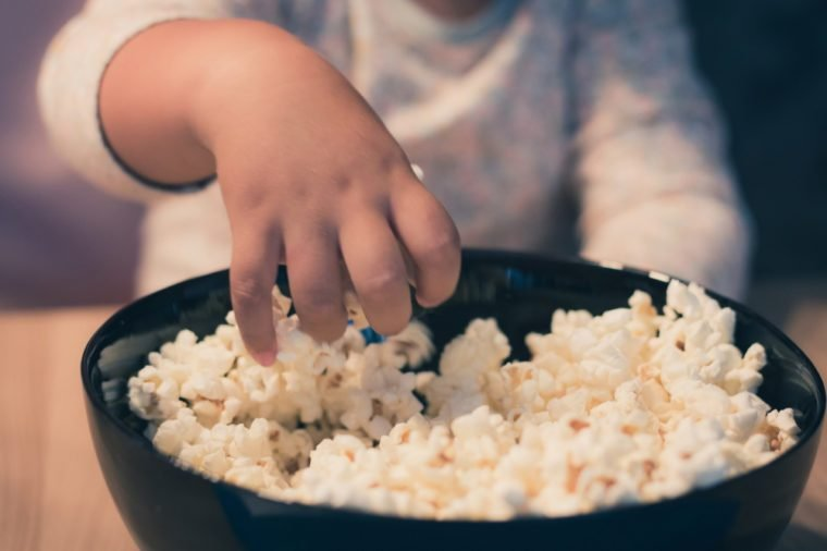 Close up of small kid eating popcorn.