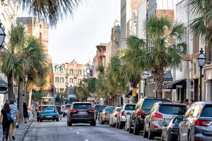 Charleston, USA - May 12, 2018: Downtown city King street in South Carolina with people walking in southern town at sunset by shops, restaurants, cars parked on road