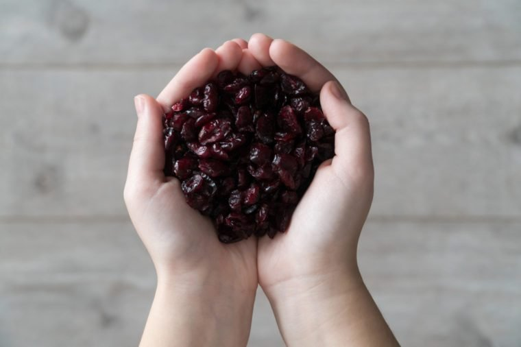 Female hands filled with dried cranberries on a bright wooden background.